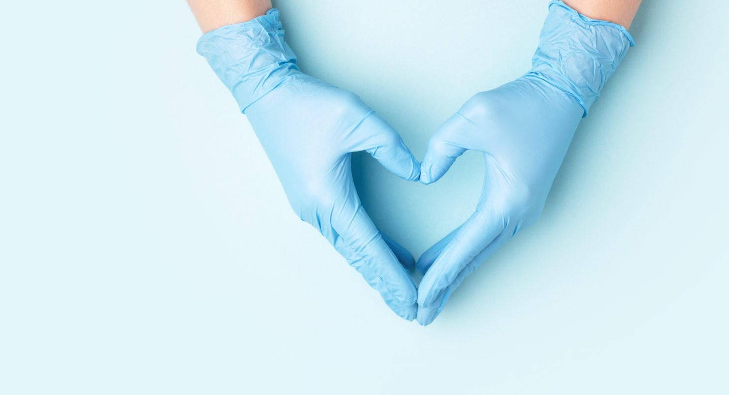 mani di un dottore che indossano i guanti e formano un cuore