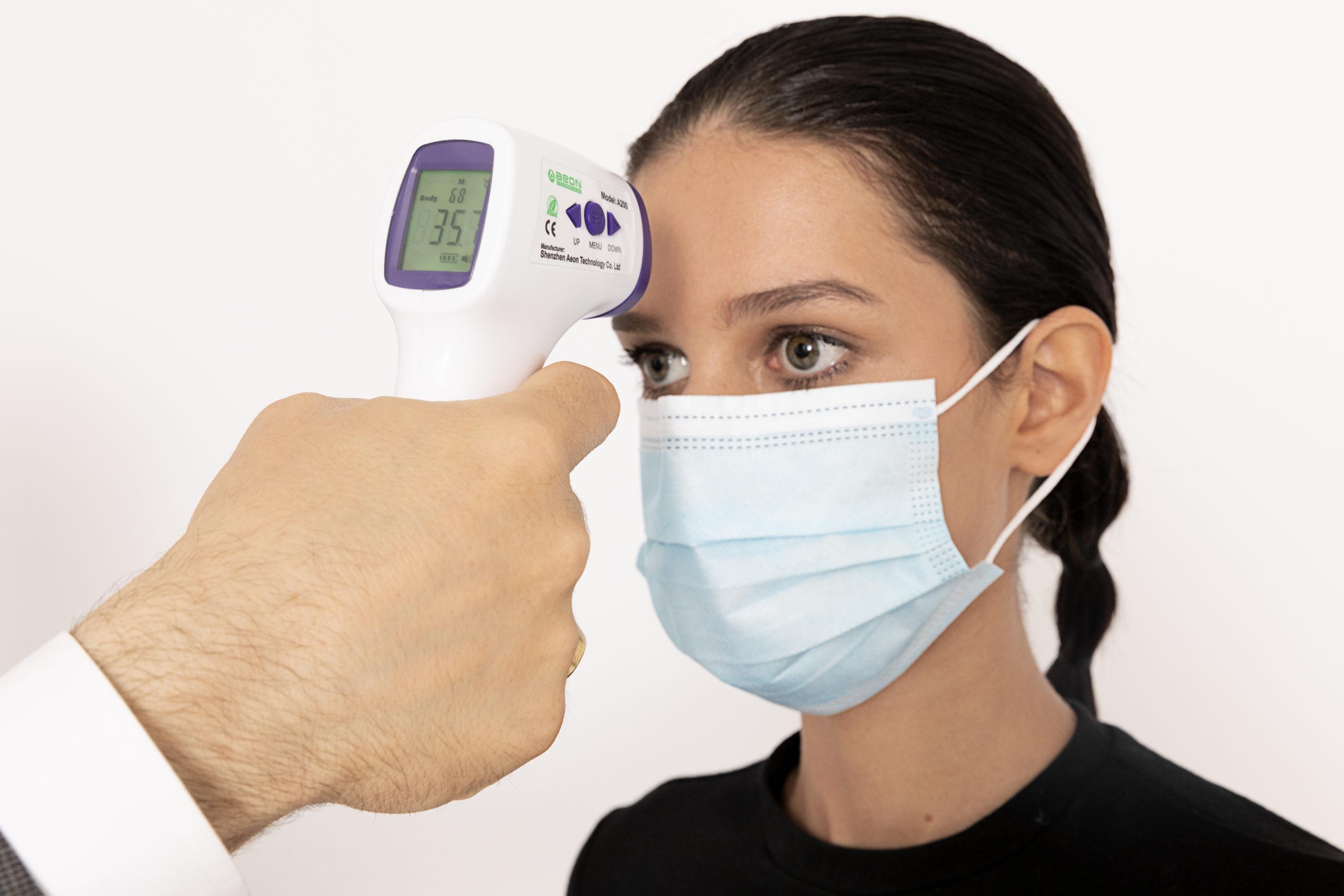immagine di una persona che prova la temperatura a distanza su di una ragazza